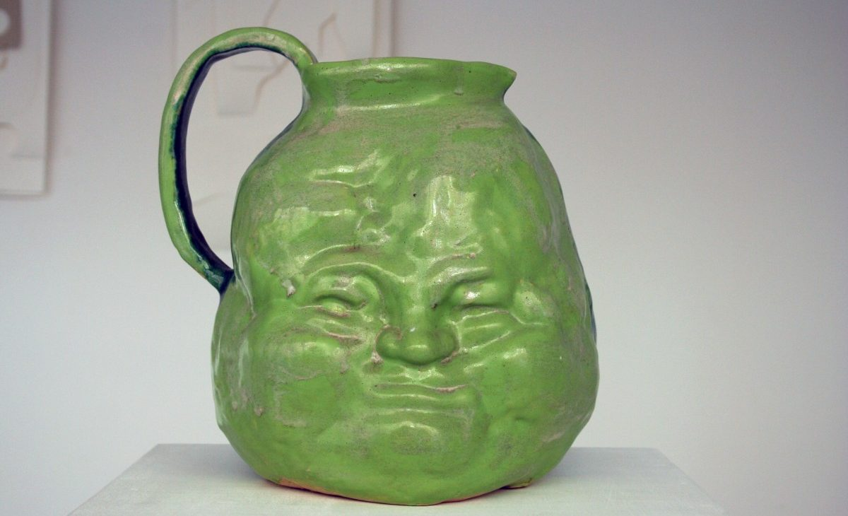 Detail shot of a green glazed earthenware jug with a scrunched up face on its side; sitting on a white plinth
