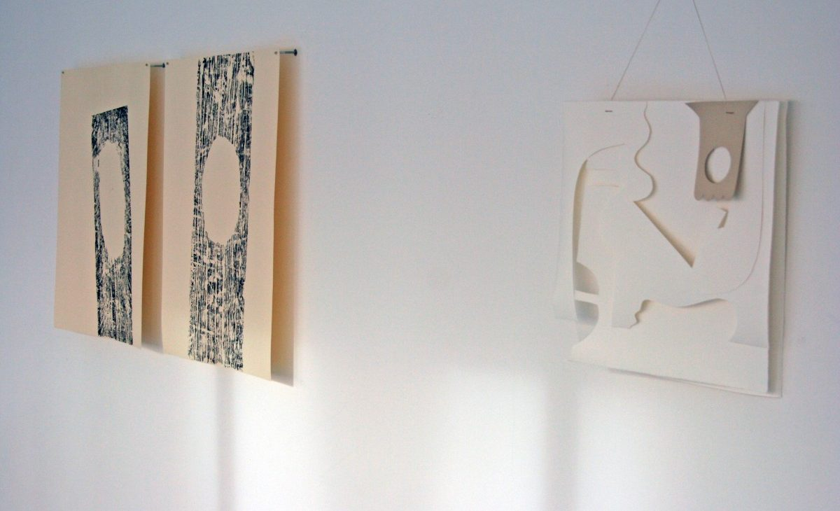 Installation view of a wall piece cut out of a paper hoover bag and two woodblock prints in black ink on paper