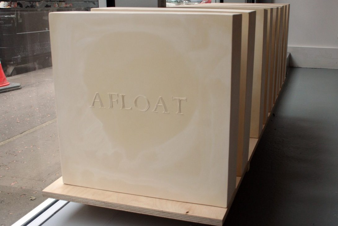 Nine Coade stone coloured slabs on a shelf against a street facing window, they are evenly spaced and the relief text on the first slab reads 'afloat' in capital letters