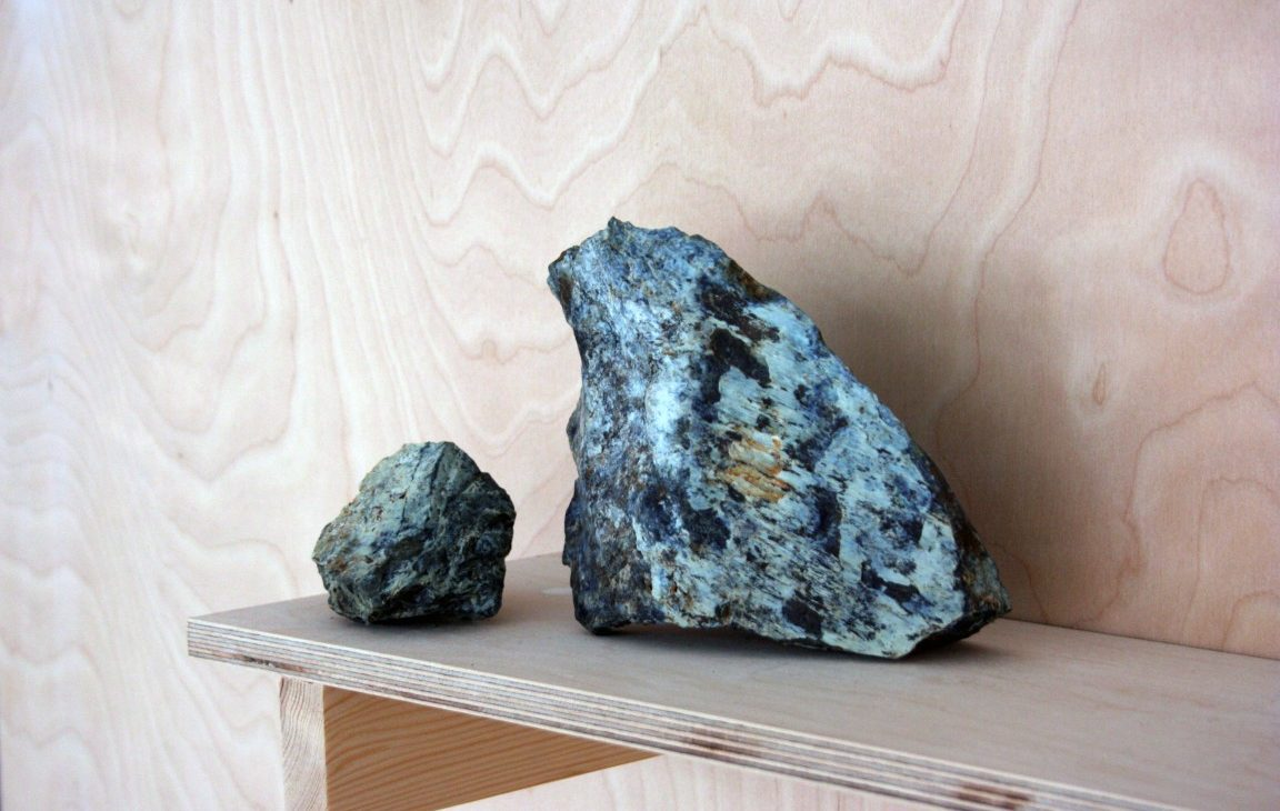 Detail of two rocks, one small and the other large, resting onm a birch plywood shelf again a plywood background