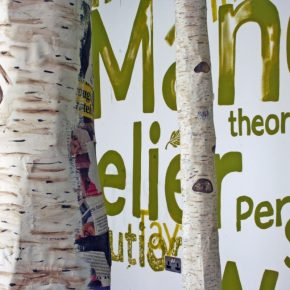 Close up of two paper mache silver birch tree trunks surrounded by alternate sizes of text painted in green on the white walls and ceiling, excerpts include: Atelier, performance, theory, Manchester