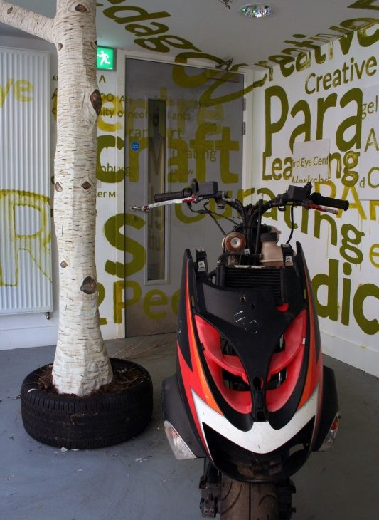 Detail view of a paper mache silver birch tree trunk sitting in a car tyre with dirt, with a red, white and black motorcycle in the foreground, surrounded by alternate sizes of text painted in green on the white walls and ceiling, and grey door, excerpts include: craft, creative, curating, learning