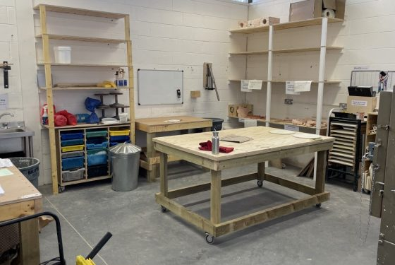 View across the Ceramic Workshop at ESW with a large wooden central table, another worktop on the left, shelving and the edge of a large electric kiln on the right.