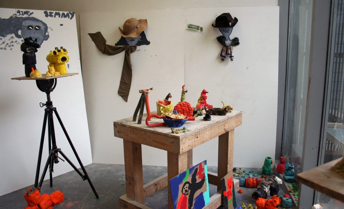 Installation view of brightly coloured ceramic sculptures displayed on a bunker, brightly coloured toilet roll and PVA animals on the floor and display stand, with painted faces on the walls in the background with hats, scarves, jewellery and other accessories