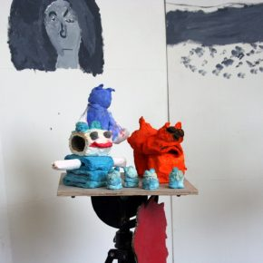 Four tiny light blue animals, a large orange cat, a blue and white smiling animal and a tall blue animal made out of toilet roll, pigments and PVA sit on top of a plywood stand. There is a face painted on the wall in the background
