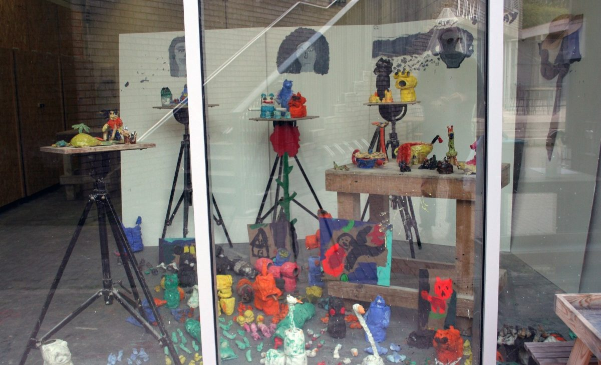 Installation view through the windows of brightly coloured ceramic sculptures displayed on a bunker, brightly coloured toilet roll and PVA animals on the floor and display stand, with painted faces on the walls in the background with hats, scarves, jewellery and other accessories