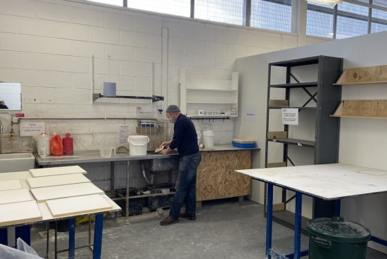 A view across the Plaster Workshop at ESW with a figure working at the far side, a worktable on the right, another work top on the left and shelving.