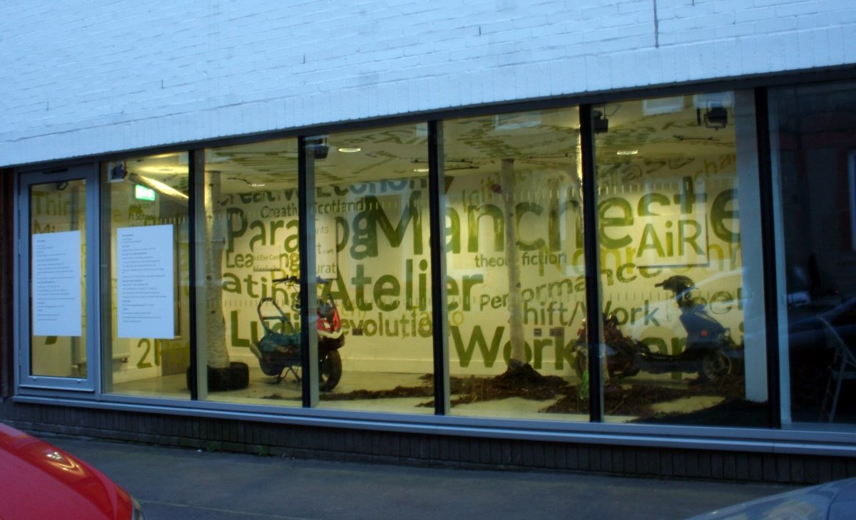 Street level view of an installation, composed of two paper mache silver birch tree trunks are surrounded by rubber tyres, motorcycles, leaves and dirt. Alternate sizes of text are painted in green on the white walls and ceiling, excerpts include: Atelier, Scotland, Economy, Devolution, Curate, Art, Craft, Resources, Learning, Peer, AiR, Glasgow, Glasgow Miracle, Manchester, futurity, medievalism. There are two large cv's on the left windows