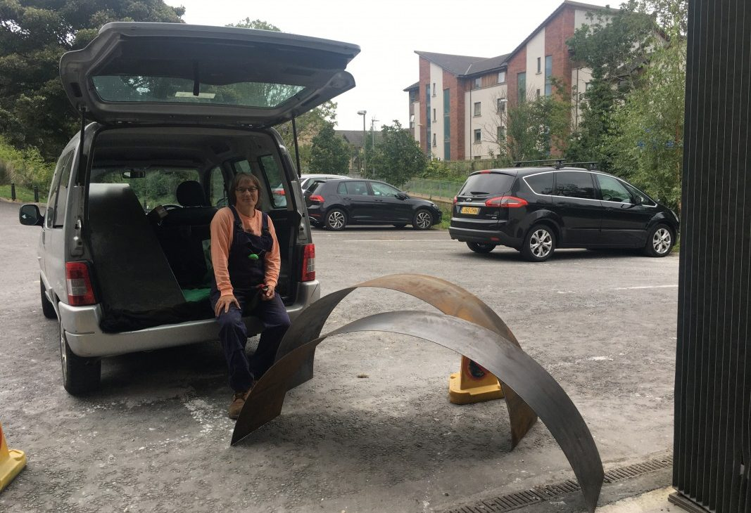 Artist Andrea Geile sitting in the boot of a car in a carpark, two rolled lengths of corten steel sheet sit on the ground in the foreground