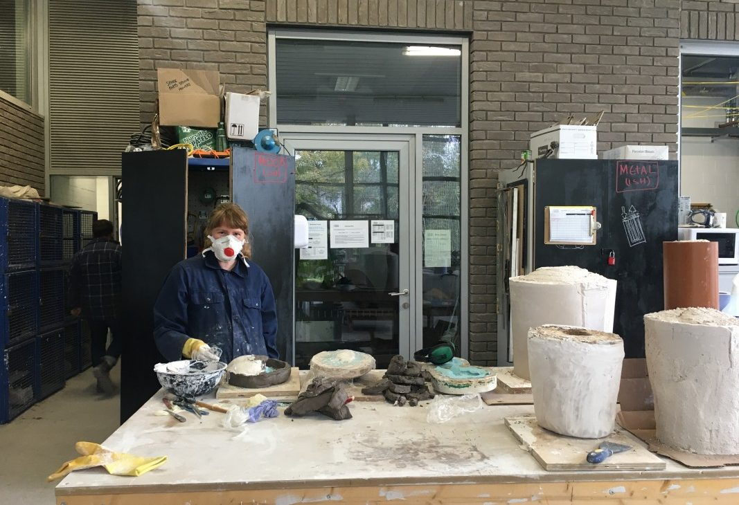 Artist Paulina Sandberg wearing P3 mask is standing on the left side of a large work table working on plaster mould jackets, there are larger moulds sitting on the other side of the table