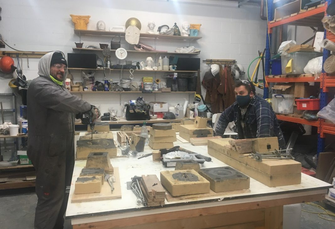Technician Stephen Murray and artist Sebastian Thomas are on either side of a large white table, the tabletop is filled with two part sand moulds