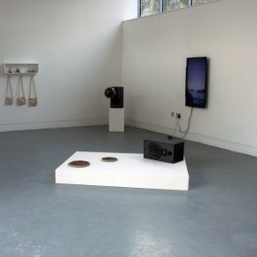 In the centre of the room two ceramic plates sit on a long white rectangular plinth alongside a black speaker on its side, two wall mounted screens, one encompassed by a black circle painted on the wall, show video work on the right, there are wall mounted ceramic works on the left