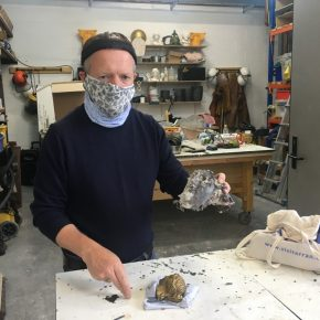 Artist Paul McAuley in a workshop holds up a bronze cast head that has remnants of sand, a smaller bronze head sits on the table in the foreground