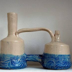 Two buff coloured stoneware pots connected by a handle between the bases of each spout and a section at the bottom of each pot. Across the bottom half of the pots is a tideline made up of waves in blue