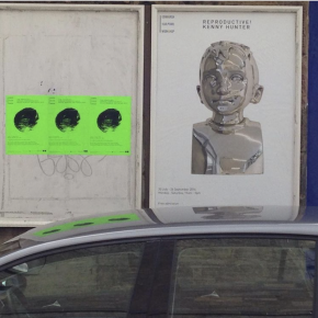Poster depicting centred image of bust of young boy in silver metal, framed within portrait hoardings, text heading on the poster is Reproduction! Kenny Hunter