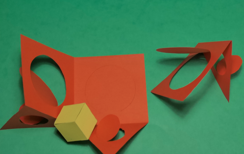 Cut paper modernist angular shapes in red and yellow paper on green background.
