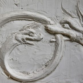 A hand modelled panel of an animal biting back onto it's tail or a snake with a face.