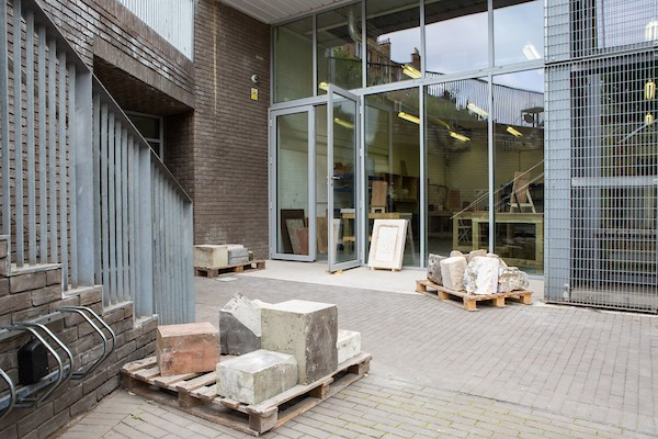 View across a patio towards the entrance to the gallery with three pallets of stone offcuts on the ground.