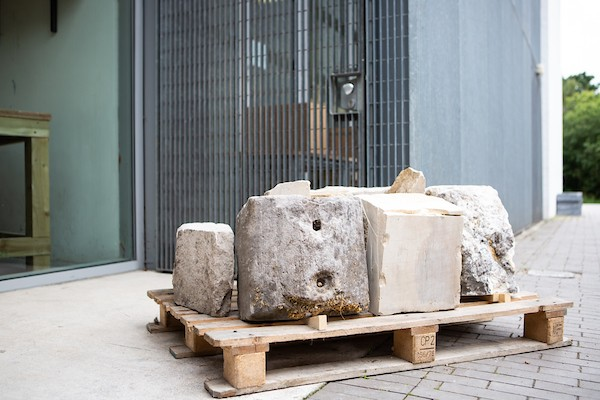 A close up of a pallet of stone offcuts, which could be used for carving sculpture from at the entrance of the exhibition.