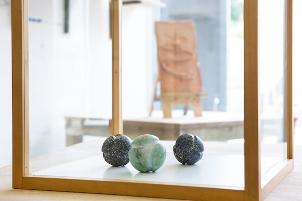 View through a transparent vitrine with three carved balls on display and a relief sculpture behind.