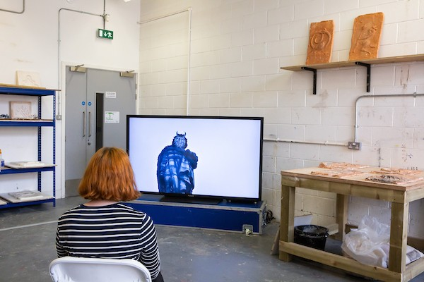 A seated person watched Sean Lynch's video within the exhibition space. A statue with an animated face is shown on the screen.