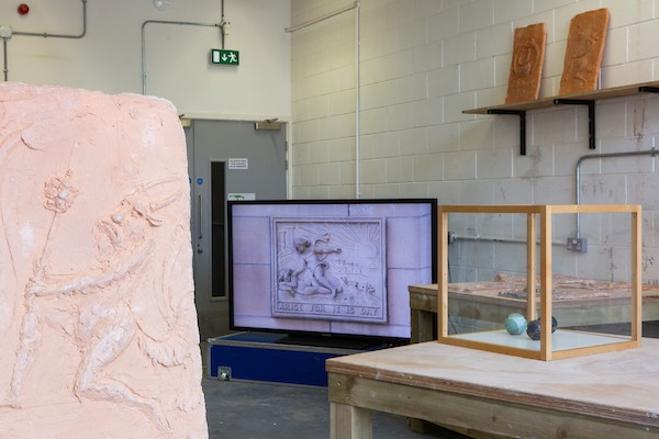 View of the exhibition showing part of a relief sculpture made from Coade stone, the video screen and the carved stone balls in a small vitrine.